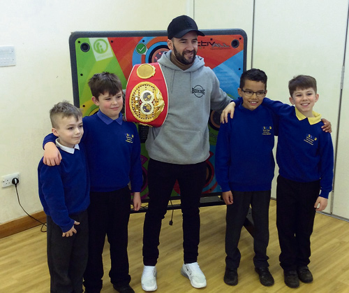 Former IBF bantamweight world champion with Barley Close Primary School children at the official launch of its reaction wall.